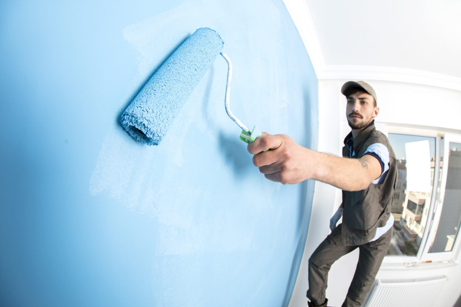 Young man painting a wall blue with a roller